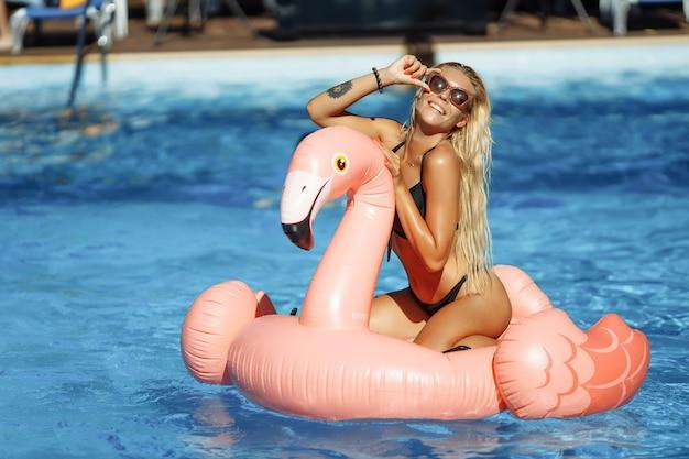 Ragazza giovane e sexy divertendosi e ridendo. divertirsi in piscina su un fenicottero rosa gonfiabile in costume da bagno e occhiali da sole in estate.