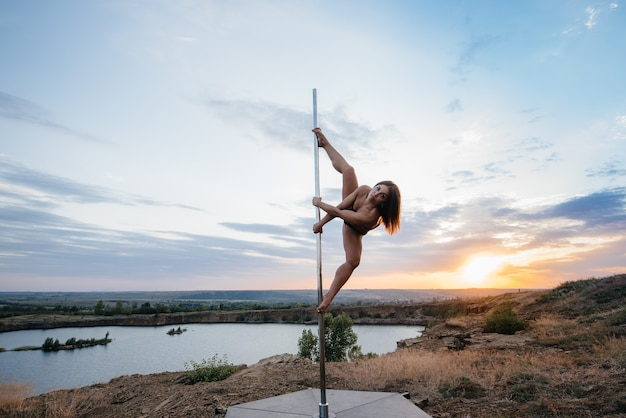 Una giovane ragazza sexy esegue incredibili esercizi su un palo durante un bellissimo tramonto. danza. sessualità.