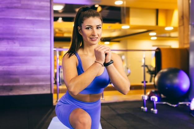 Giovane ragazza sexy esegue un riscaldamento in palestra e posa in vestiti blu