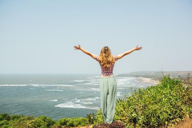 Giovane ragazza sexy rilassata vicino al mare in vacanza estiva bella giornata calda, abbigliamento casual, godetevi, donna felice, rilassante, in viaggio, attraente, stile, modello