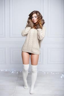 Giovane ragazza sexy in vestiti caldi e guanti lavorati a maglia in piedi vicino al muro della stanza