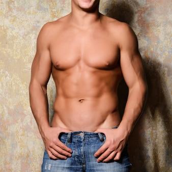 Giovane uomo macho muscoloso sexy in posa con il torso nudo.
