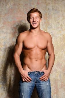 Giovane uomo macho muscoloso sexy in posa con il torso nudo