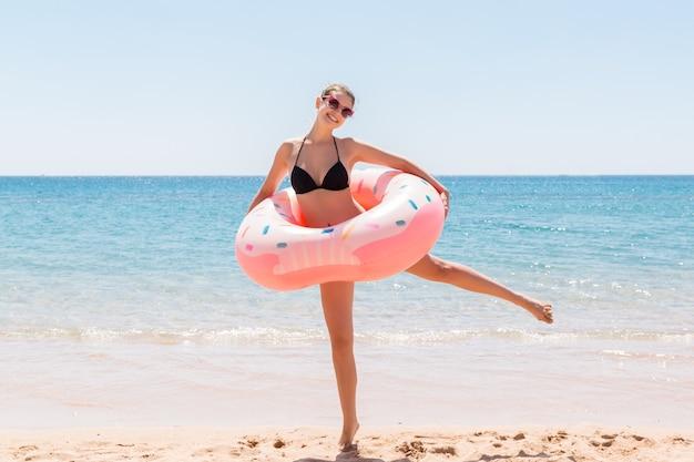 La giovane donna graziosa sexy resta sulla spiaggia del mare e gioca con la ciambella gonfiabile dell'anello e si diverte. vacanze estive e concetto di vacanza.