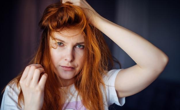 La giovane ragazza dai capelli rossi sexy tocca i suoi capelli arruffati e guarda la macchina fotografica, primo piano. bella pelle e capelli ben curati. immagine per la pubblicità dell'industria della bellezza e della cosmetologia.