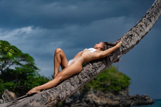 Giovane donna sexy in bikini sdraiato sul cielo drammatico di palma spirito sullo sfondo. concetto di salute e benessere.