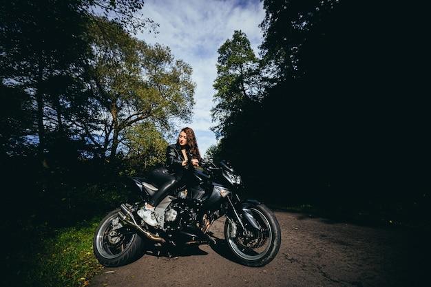 Giovane donna sexy in una giacca di pelle nera che si siede su una moto sportiva nera sullo sfondo di una bella strada forestale