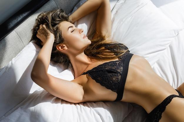 Giovane donna sexy in lingerie nera sdraiata sul letto