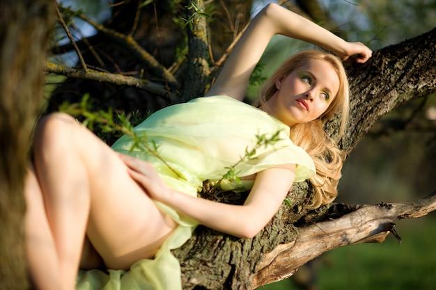 Giovane donna sexy in vestito verde che si siede sul tronco di albero sopra l'acqua il giorno di estate con la natura verde