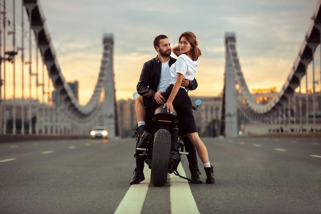 Giovane donna sexy che abbraccia uomo carino in giacca di pelle nera elegante, seduto su moto sportiva sul ponte della città al tramonto e baciare.