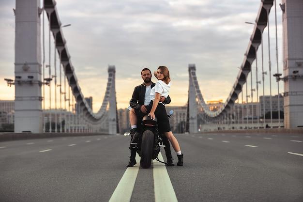 Giovane donna sexy che abbraccia uomo carino in elegante giacca di pelle nera, seduto sulla moto sportiva sul ponte della città sul tramonto