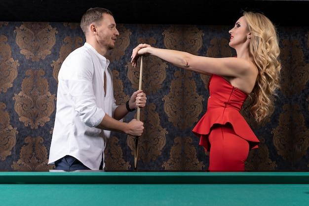 Giovane donna sexy e uomo si guardano con un sorriso e tenerezza mentre giocano a biliardo insieme tenendo una stecca di legno