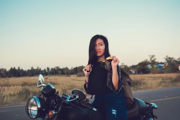 Giovane donna sexy su una moto in natura sul tramonto. concetto di viaggio