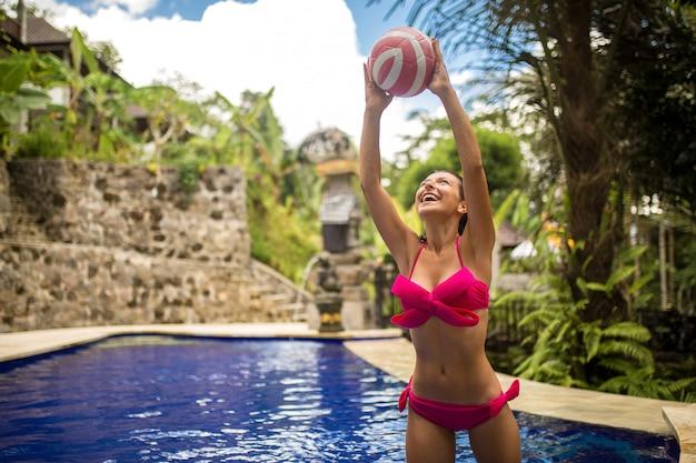 La giovane donna sexy in costume da bagno rosa gioca con la palla nella piscina tropicale