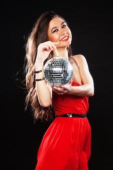 Giovane donna sexy in abiti rossi che tiene la palla da discoteca