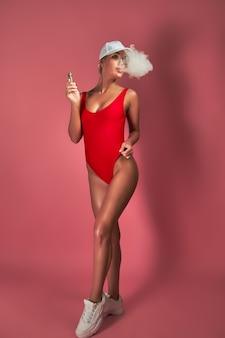 La giovane donna sexy in costume da bagno rosso e berretto sta svapando posando su sfondo rosa studio una nuvola di vapore