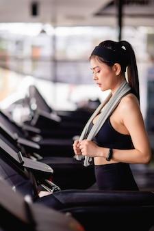 Giovane donna sexy che indossa abbigliamento sportivo, tessuto resistente al sudore e smartwatch che cammina sul tapis roulant si riscalda prima di correre per allenarsi nella palestra moderna, spazio copia