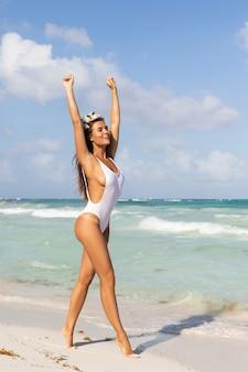 Giovane donna sexy che indossa il costume da bagno bianco è in posa sulla spiaggia