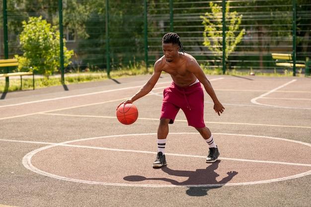 Giovane giocatore di basket shirtles spostandosi verso il basso parco giochi durante l'allenamento con la palla durante l'allenamento