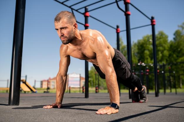 Giovane atleta a torso nudo che suda stando in piedi sulle braccia tese sul campo sportivo mentre pratica le flessioni