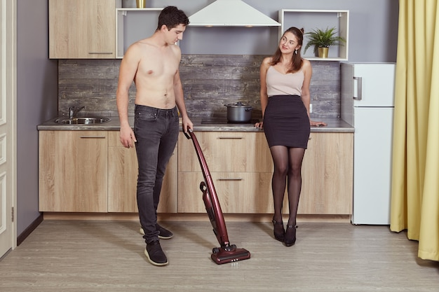Il giovane uomo caucasico senza camicia sta pulendo la cucina con l'aiuto dell'aspirapolvere senza fili mentre la sua ragazza attraente lo sta guardando.
