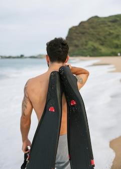 Giovane uomo a torso nudo sulla spiaggia con attrezzatura subacquea