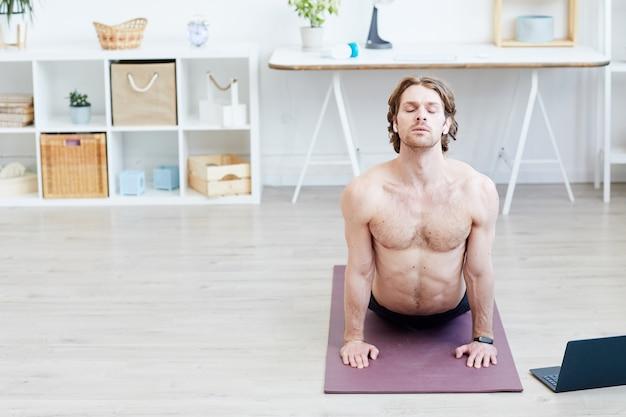 Giovane uomo a torso nudo facendo esercizi di stretching sulla stuoia di esercizio nel soggiorno di casa
