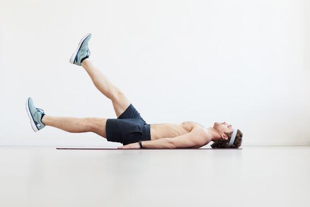 Giovane uomo a torso nudo sdraiato sul pavimento e alzando la gamba isolata su sfondo bianco