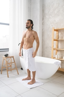 Giovane uomo a torso nudo con morbido asciugamano bianco sui fianchi in piedi sul piccolo tappeto dopo aver fatto un bagno caldo con schiuma