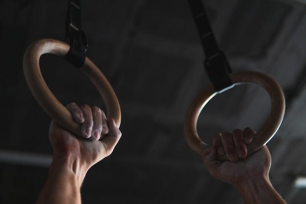 Giovane atleta muscolare senza camicia che si prepara a fare stacco in una palestra di crossfit