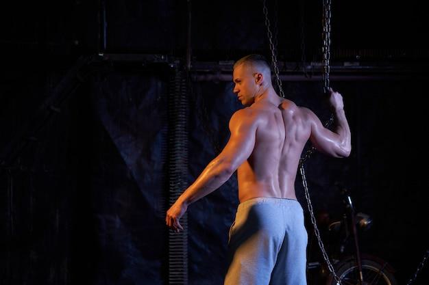 Giovane uomo muscoloso torso nudo in piedi tra catene di metallo, guardando seriamente la fotocamera, copia lo spazio con le spalle alla telecamera