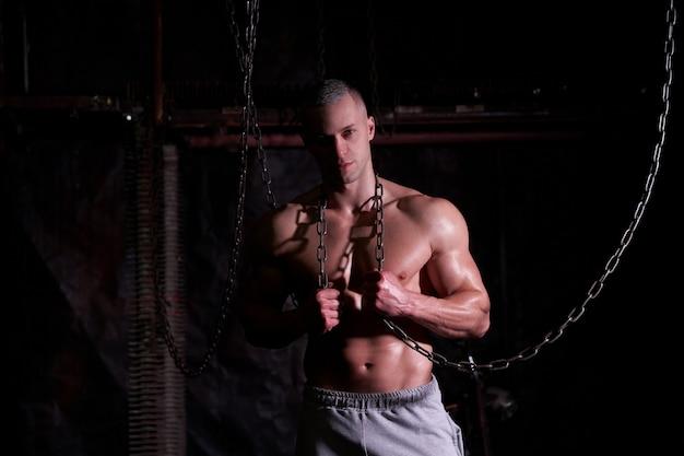Giovane uomo muscoloso senza camicia in piedi tra catene di metallo, guardando seriamente la telecamera, copia spazio