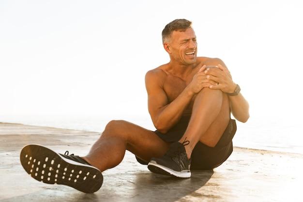 Giovane sportivo senza camicia che soffre di un dolore al ginocchio