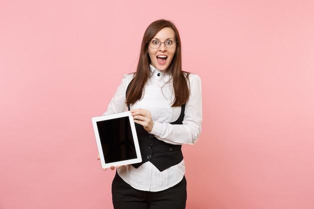 Giovane donna d'affari stupita scioccata in tuta e occhiali che tengono computer tablet pc con schermo vuoto vuoto isolato su sfondo rosa pastello. signora capo. concetto di ricchezza di carriera di successo. copia spazio.