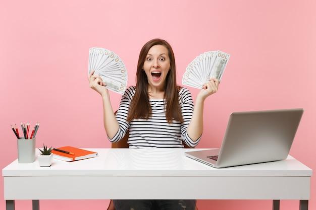 Giovane donna scioccata e stupita che tiene in mano un sacco di dollari in contanti che lavorano in ufficio alla scrivania bianca con un computer portatile