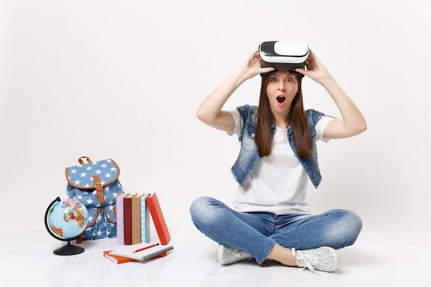 Giovane studentessa stupita scioccata che rimuove gli occhiali per realtà virtuale godendosi seduta vicino al globo, zaino, libri scolastici isolati su muro bianco