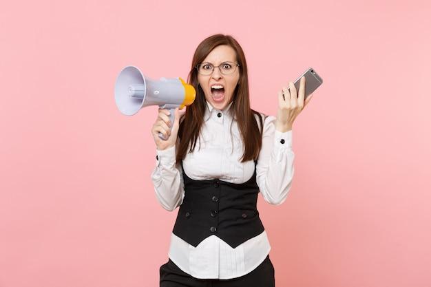 Giovane donna d'affari arrabbiata scioccata in abito nero, occhiali urlanti che tengono megafono e telefono cellulare isolato su sfondo rosa. signora capo. ricchezza di carriera di successo. copia spazio per la pubblicità.