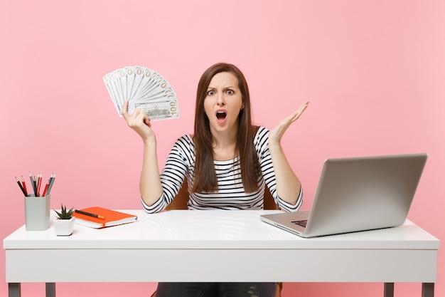 Giovane donna scioccata e sconcertata che allarga le mani con un sacco di dollari in denaro contante lavora in ufficio alla scrivania bianca con un computer portatile
