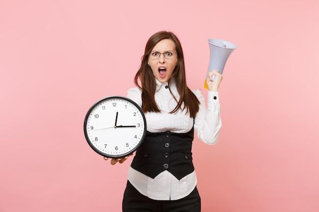 Giovane donna d'affari scioccata con gli occhiali che urla tenendo il megafono e la sveglia isolati su sfondo rosa pastello. signora capo. concetto di ricchezza di carriera di successo. copia spazio per la pubblicità.