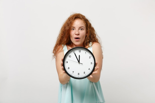 Giovane ragazza di donna rossa stupita eccitata scioccata in vestiti leggeri casuali in posa isolata sul fondo bianco della parete, ritratto in studio. concetto di stile di vita della gente. mock up copia spazio. tenendo l'orologio rotondo.