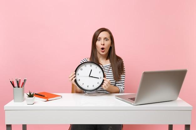 Giovane donna perplessa scioccata che tiene la sveglia rotonda mentre è seduta a lavorare in ufficio con un computer portatile