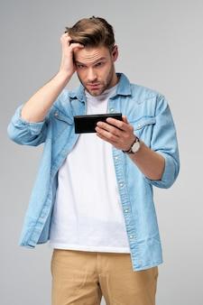 Giovane uomo arrabbiato e frustrato stressato scioccato utilizzando smartphone