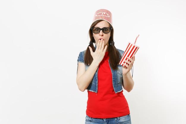 Giovane donna scioccata in occhiali 3d con secchio per popcorn sulla testa guardando film, tenendo in mano una tazza di plastica di soda o cola, coprendo la bocca con il palmo isolato su sfondo bianco. emozioni al cinema.