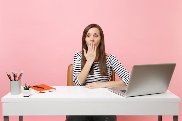 Giovane donna scioccata in abiti casual che copre la bocca con il palmo della mano, lavora alla scrivania bianca con un computer portatile contemporaneo