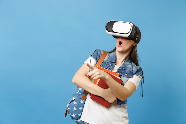 La giovane studentessa scioccata con la bocca aperta con lo zaino in occhiali per realtà virtuale tiene i libri di scuola che puntano il dito indice isolato su sfondo blu. istruzione al college universitario di scuola superiore.