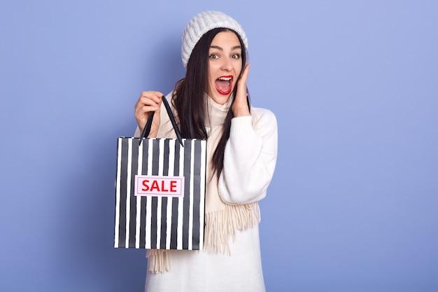 Giovane signora shoked che sta tenendo i sacchetti della spesa a strisce in bianco e nero con la vendita dell'iscrizione