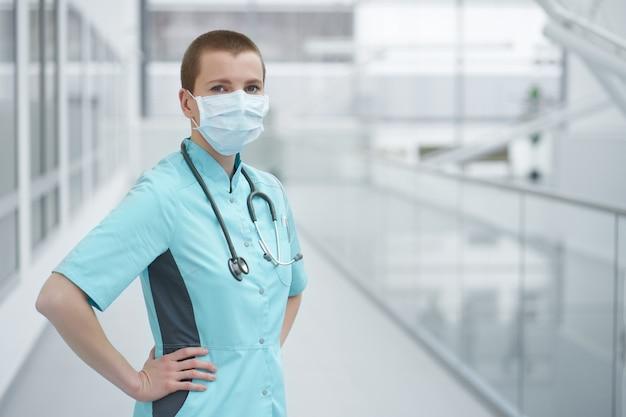 Medico di donna caucasica giovane scorciatoia, indossando maschera medica, copia spazio ritratto