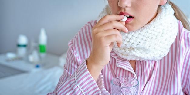 La giovane ragazza ammalata mette una pillola in bocca