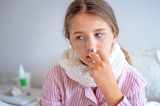 La giovane ragazza ammalata si spruzza il naso con uno spray nasale.
