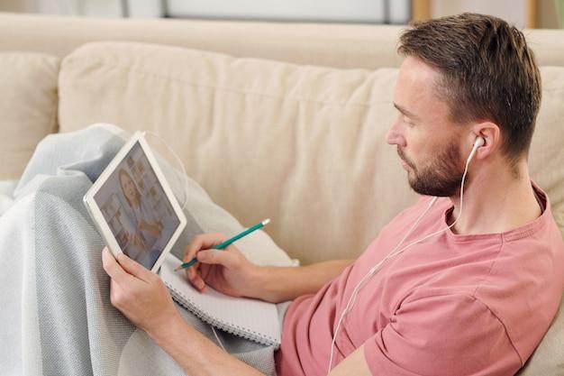 Giovane malato con gli auricolari seduto sul divano sotto la coperta, prendendo appunti e consultando un medico online mentre tiene un tablet digitale sulle ginocchia
